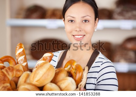 smiling salesgirl working in bakery and holding basket with bread loafs