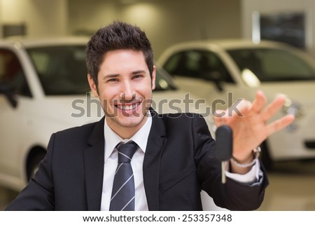 Smiling salesman giving a customer car keys at new car showroom