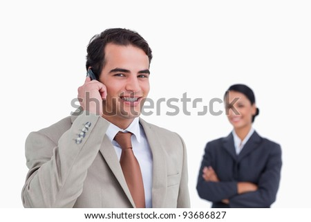 Smiling salesman on his cellphone with colleague behind him against a white background - stock photo