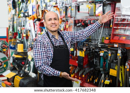 Smiling salesman showing different tools and instruments in wholesale