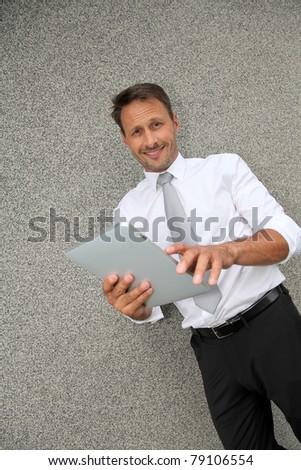Smiling salesman using electronic tablet - stock photo