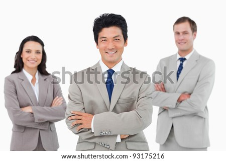 Smiling salesteam with arms folded against a white background - stock photo