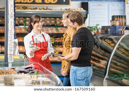 Smiling saleswoman assisting couple in buying meat at butcher's shop - stock photo