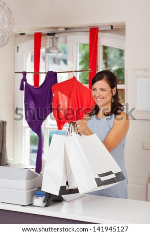 Smiling saleswoman giving shopping bags to female customer in boutique