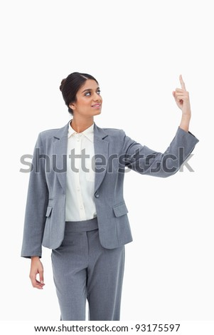 Smiling saleswoman pointing up against a white background