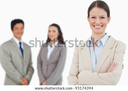 Smiling saleswoman with arms folded and associates behind her against a white background