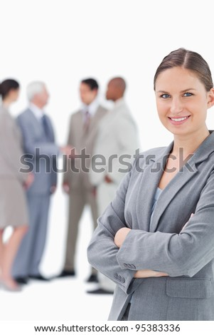 Smiling saleswoman with arms folded and colleagues behind her against a white background