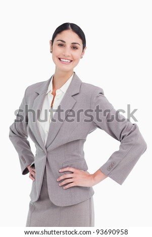 Smiling saleswoman with hands on her hip against a white background