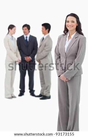 Smiling saleswoman with her team behind her against a white background - stock photo