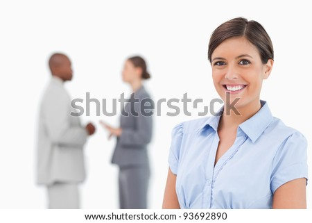 Smiling saleswoman with talking colleagues behind her against a white background