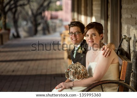 Smiling same sex bride and groom seated together