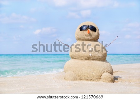 Smiling sandy happy man in sunglasses on the sea beach against blue cloudy summer sky - travel concept
