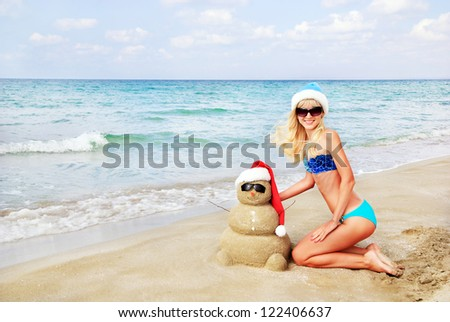 Smiling sandy snowman in red santa hat and attractive blonde woman on the sea beach. Holiday concept can be used for New Year and Christmas Cards