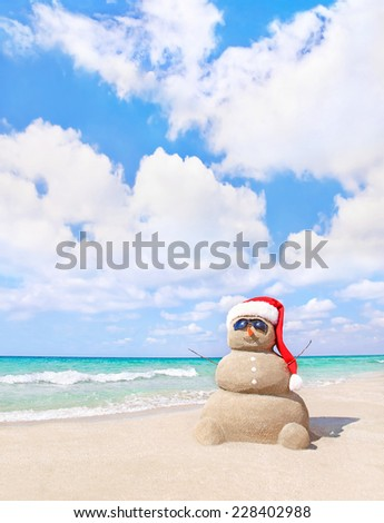 Smiling sandy snowman in red santa hat on sea beach. New Years and Christmas holidays in hot countries concept. - stock photo