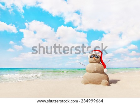 Smiling sandy snowman in red santa hat on sea beach. New Years and Christmas holidays in hot countries concept - stock photo