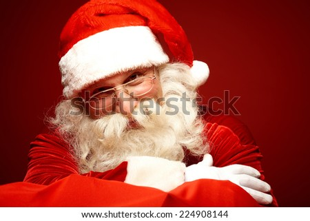 Smiling Santa Claus in eyeglasses posing for camera - stock photo