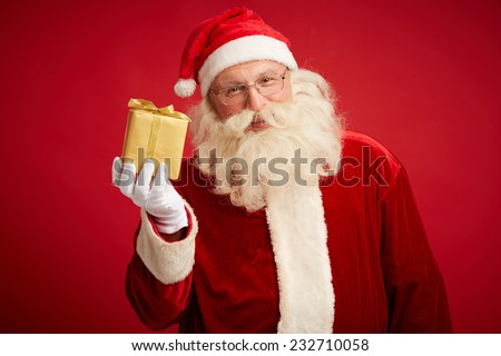 Smiling Santa Claus showing golden package and looking at camera - stock photo