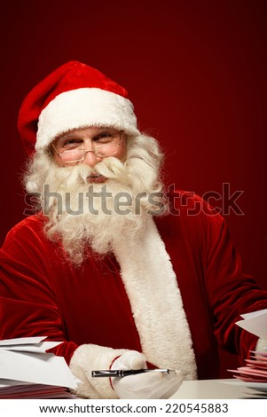 Smiling Santa Claus with pen looking at camera while answering Christmas letters