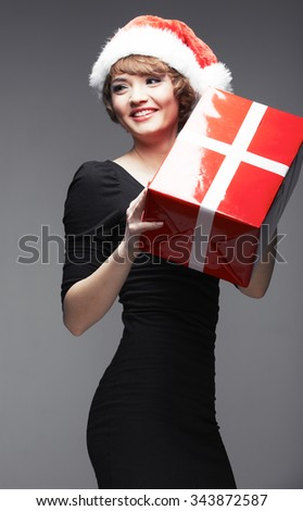 Smiling Santa girl. Sexy young woman posing with red gift box. Studio gray isolated.