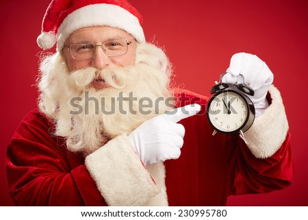 Smiling Santa pointing at alarm clock in his hand showing five minutes to twelve - stock photo