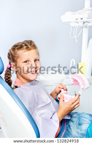 Smiling school aged girl cleaning toy dentures with a toothbrush - stock photo
