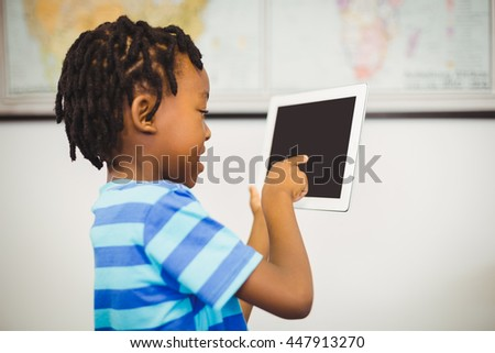 Smiling school boy using a digital tablet in classroom at school - stock photo