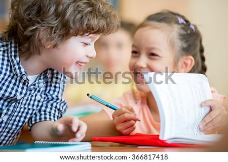 Smiling school children in classroom - stock photo