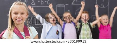 Smiling school girl, in the background group of excited children raising their hands, panorama