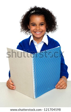 Smiling school girl learning weekly assignment. Looking confident before the examinations.