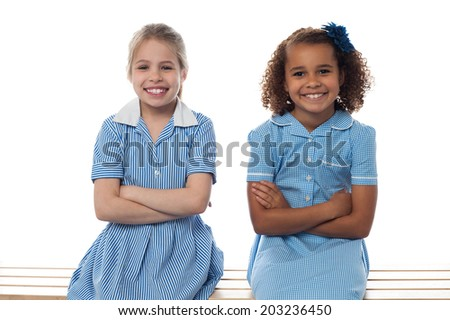 Smiling school girls sitting in bench, arms folded - stock photo