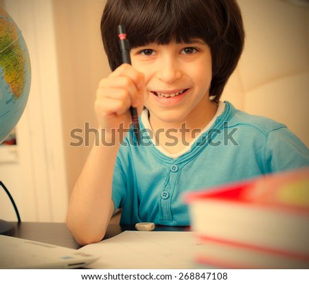smiling schoolboy doing homework. instagram image retro style - stock photo