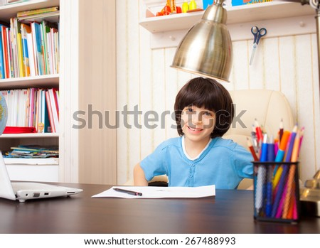 smiling schoolboy doing homework, portrait