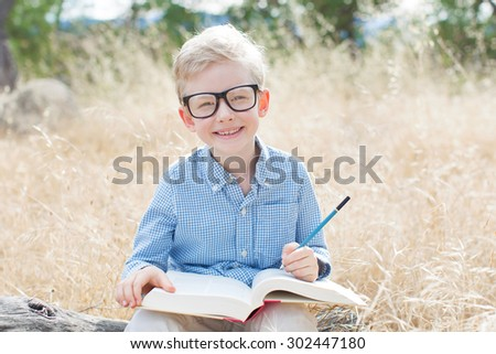 smiling schoolboy in glasses studying ready for school enjoying warm weather in the park - stock photo