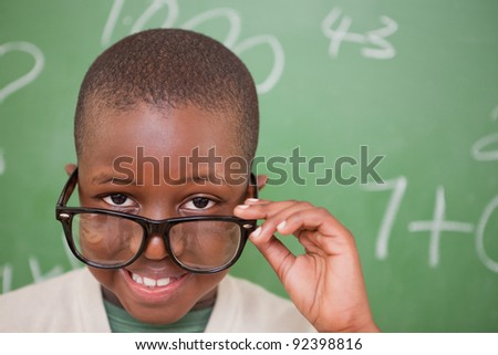 Smiling schoolboy looking over his glasses in front of a blackboard - stock photo