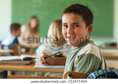 Smiling schoolboy sitting at his desk at school. - stock photo