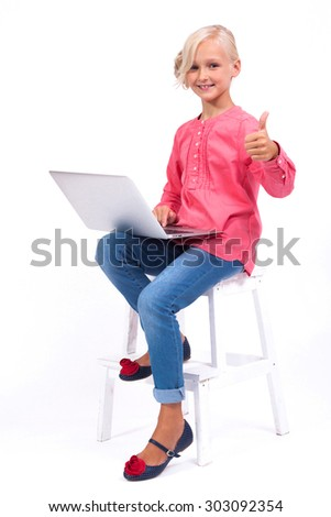 Smiling schoolgirl learns and communicates with the help of modern tablets and phones, an interesting training and communication gadgets. Photo from the depth of field  - stock photo