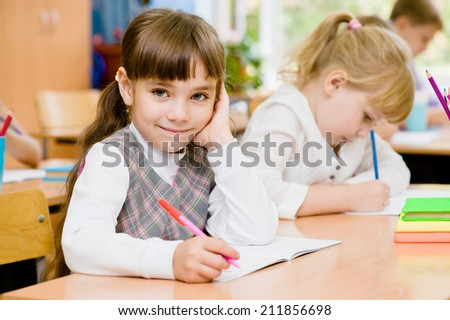 smiling schoolgirl looking at camera during lesson - stock photo