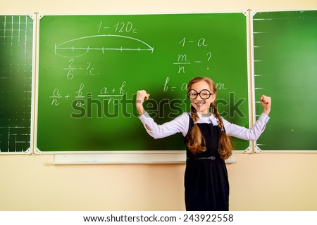 Smiling schoolgirl performs the task at the blackboard. Education. - stock photo