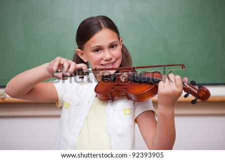 Smiling schoolgirl playing the violin in a classroom - stock photo