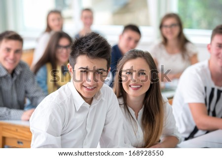 Smiling schoolgirl posing with classmate in classroom - stock photo