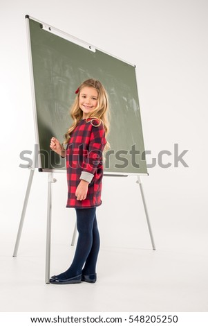 Smiling schoolgirl standing near chalkboard on grey