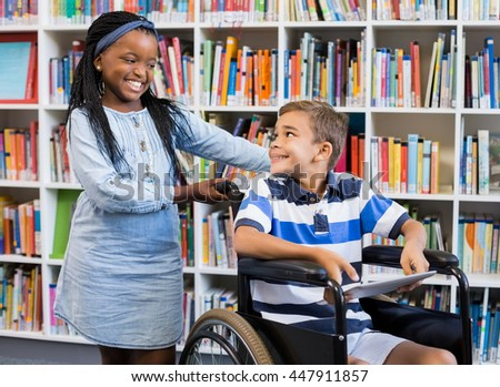 Smiling schoolgirl standing with disabled boy on wheelchair in library