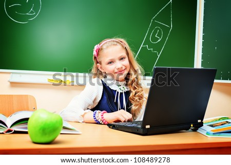 Smiling schoolgirl studying with her laptop at classroom. - stock photo