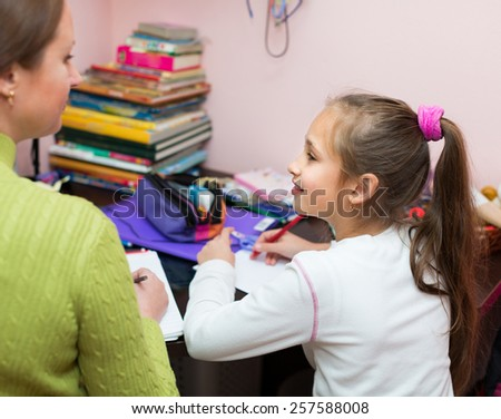 Smiling schoolgirl with mother doing homework in home together   - stock photo