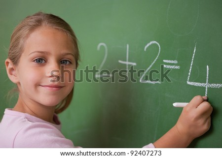 Smiling schoolgirl writing a number in a blackboard - stock photo