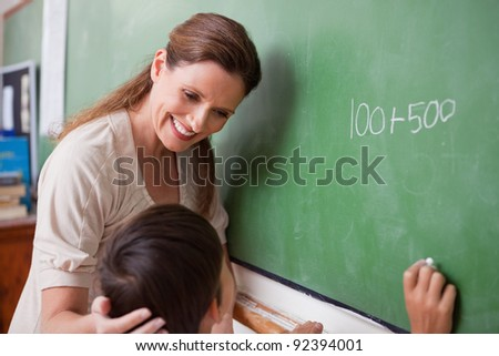Smiling schoolteacher helping a schoolboy doing an addition on a blackboard - stock photo