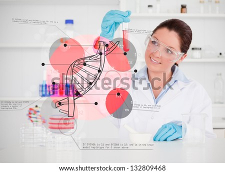 Smiling scientist examining test tube with dna helix holographic interface - stock photo