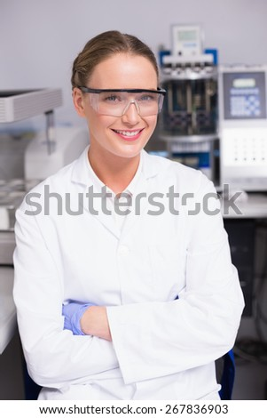 Smiling scientist looking at camera arms crossed in laboratory