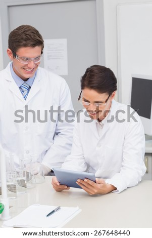 Smiling scientists using tablet in laboratory