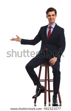 smiling seated businessman is presenting something on white background